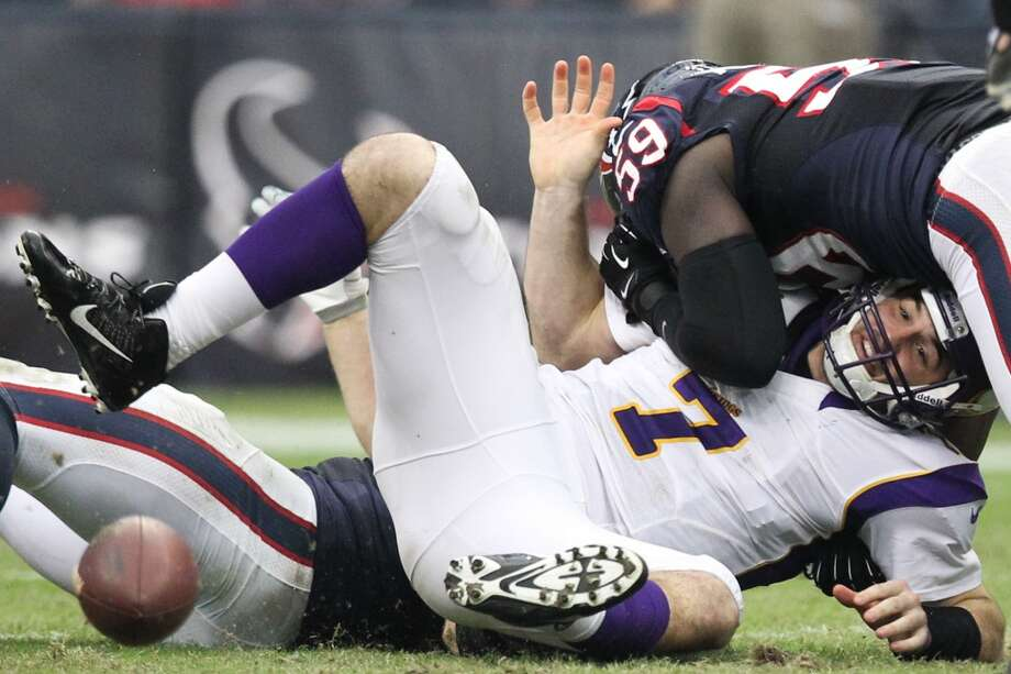 Vikings quarterback Christian Ponder (7) fumbles as he is hit by Texans linebacker Whitney Mercilus (59) and defensive end J.J. Watt (99) during the third quarter. (Nick de la Torre / Houston Chronicle)