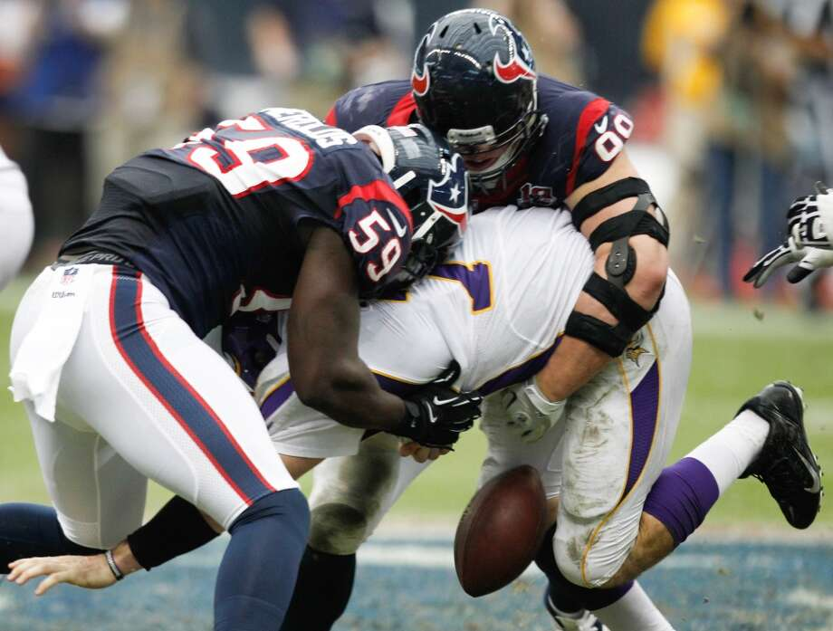 Texans linebacker Whitney Mercilus (59) and defensive end J.J. Watt (99) force a fumble as they sack Vikings quarterback Christian Ponder (7) during the third quarter. (Brett Coomer / Houston Chronicle)