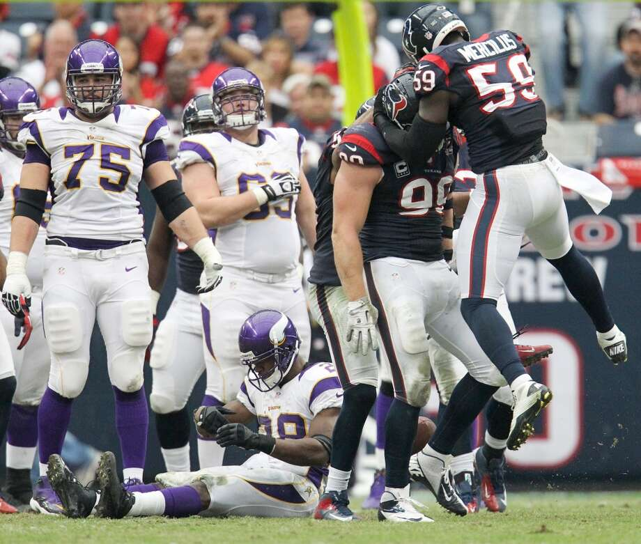 Texans defenders celebrates stopping Minnesota Vikings running back Adrian Peterson during the third quarter. (Karen Warren / Houston Chronicle)