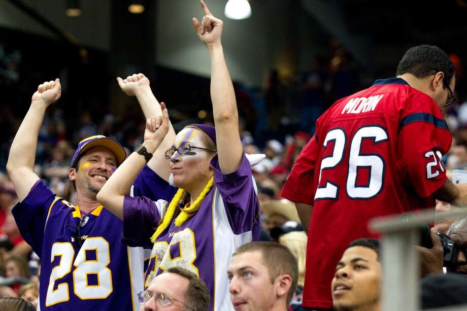 A pair of Vikings fans celebrate the Vikings win over the Texans during the fourth quarter. (Brett Coomer / Houston Chronicle)