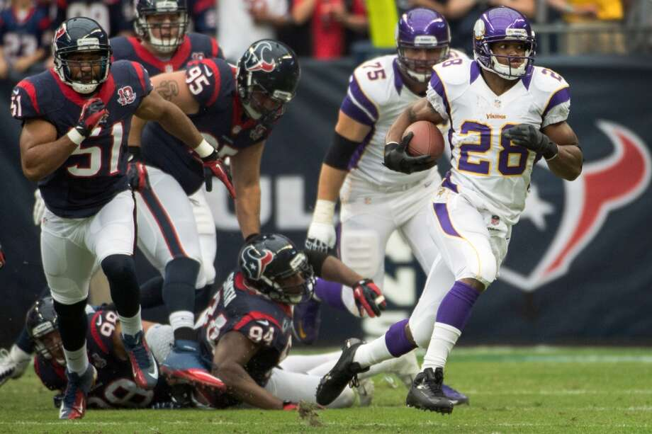 Vikings running back Adrian Peterson (28) gets past Texans linebacker Connor Barwin (98), defensive end Antonio Smith (94), nose tackle Shaun Cody (95) and linebacker Darryl Sharpton (51) on a 20-yard gain during the first quarter. (Smiley N. Pool / Houston Chronicle)