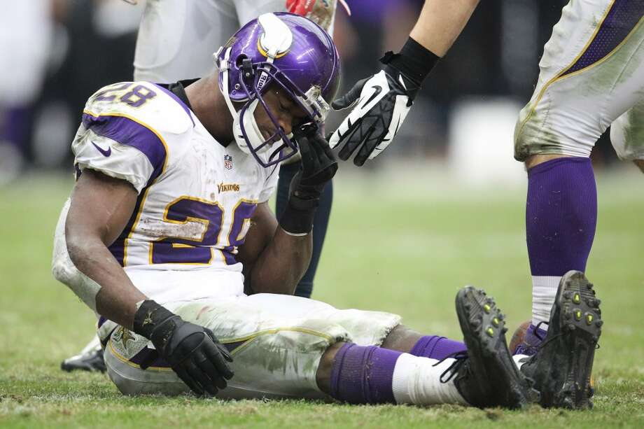 Vikings running back Adrian Peterson sits on the field picking grass out of his helmet during the third quarter. (Karen Warren / Houston Chronicle)