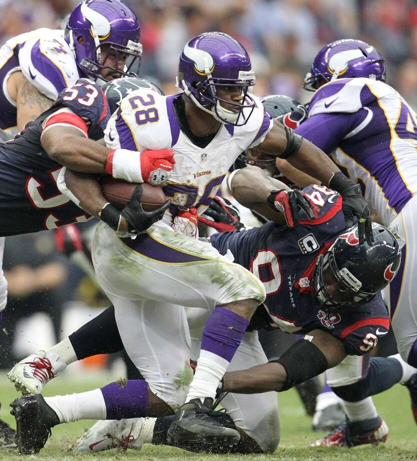 Vikings running back Adrian Peterson (28) is brought down by Texans inside linebacker Bradie James (53) and defensive end Antonio Smith (94) during the third quarter. (Karen Warren / Houston Chronicle)