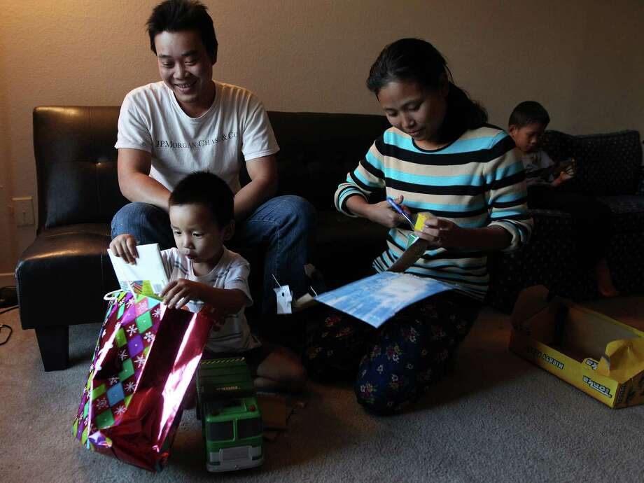 Ler Htoo, left, and Sheu Ro Paw help their son, Sha Ler Soe, open his gifts in their southwest Houston apartment. For the first time, the Burmese family can celebrate Christmas without fear of persecution or censure. Photo: Mayra Beltran, Staff / © 2012 Houston Chronicle