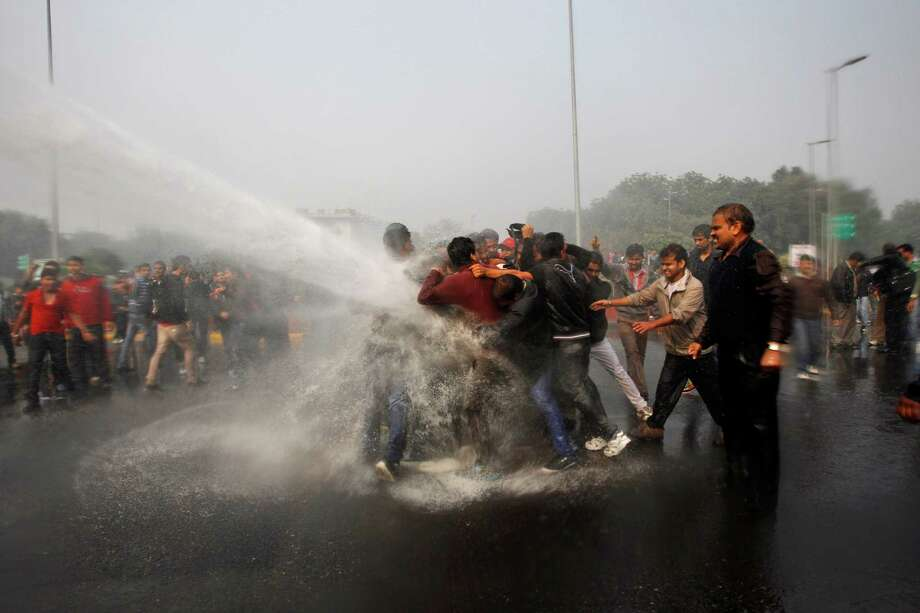 Indian police use water cannon to disperse protesters demonstrating against a gang rape and brutal beating of a 23-year-old student on a bus in New Delhi, India, Sunday, Dec. 23, 2012. The attack last Sunday has sparked days of protests across the country. (AP Photo/Tsering Topgyal) Photo: Tsering Topgyal