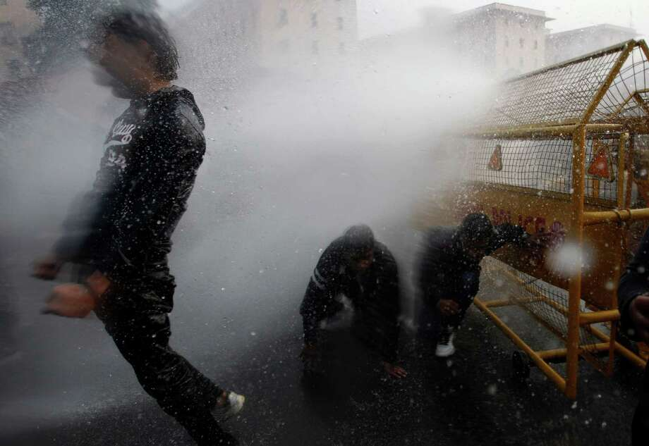 Indian police use water cannon to disperse protesters demonstrating against a gang rape and brutal beating of a 23-year-old student on a bus, in New Delhi, India, Sunday, Dec. 23, 2012. The attack last Sunday has sparked days of protests across the country. (AP Photo/Tsering Topgyal) Photo: Tsering Topgyal