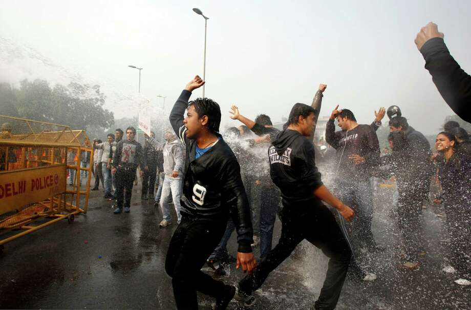 Indian protesters shout slogans as policemen use water cannon to disperse those demonstrating against a gang rape and brutal beating of a 23-year-old student on a bus, in New Delhi, India, Sunday, Dec. 23, 2012. The attack last Sunday has sparked days of protests across the country. (AP Photo/Tsering Topgyal) Photo: Tsering Topgyal