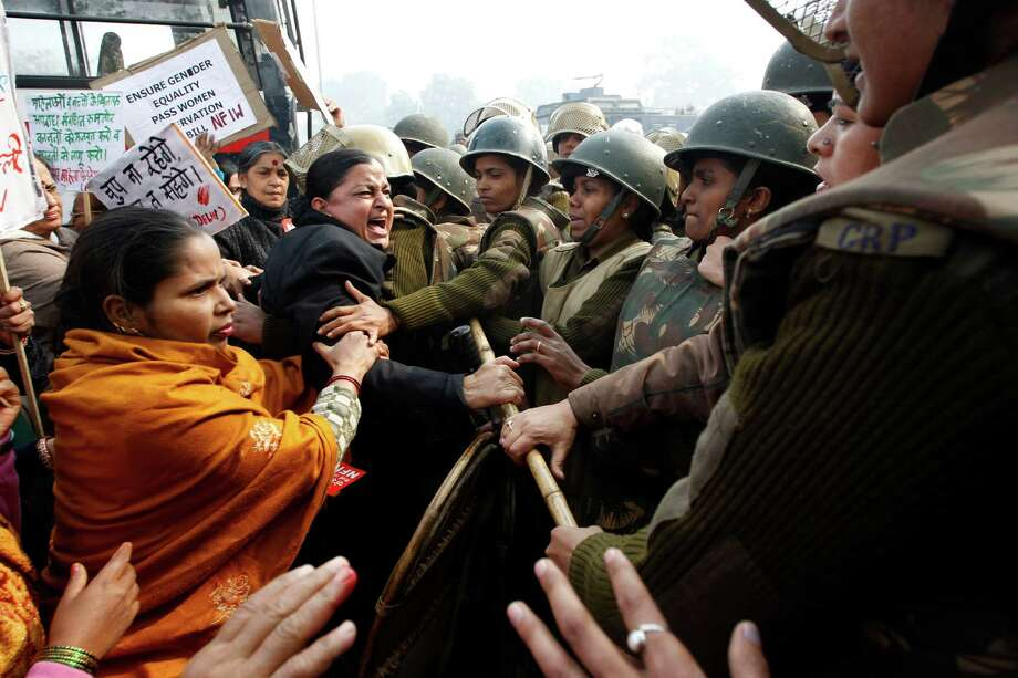 Indian police try to stop women protesters demonstrating against a gang rape and brutal beating of a 23-year-old student on a bus in New Delhi, India, Sunday, Dec. 23, 2012. The attack last Sunday has sparked days of protests across the country. (AP Photo/Tsering Topgyal) Photo: Tsering Topgyal