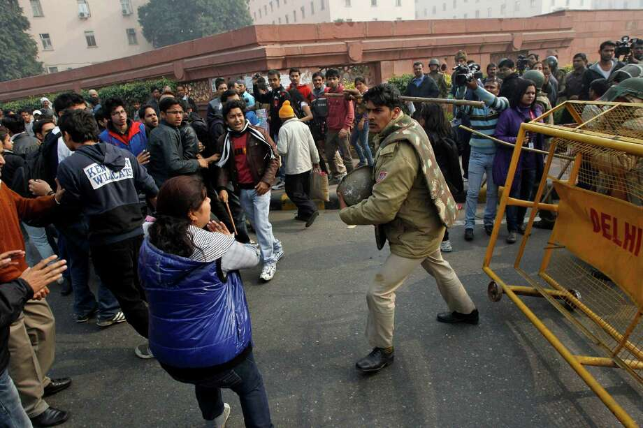 An Indian policeman baton charges to disperse protesters demonstrating against a gang rape and brutal beating of a 23-year-old student on a bus in New Delhi, India, Sunday, Dec. 23, 2012. The attack last Sunday has sparked days of protests across the country. (AP Photo/Tsering Topgyal) Photo: Tsering Topgyal