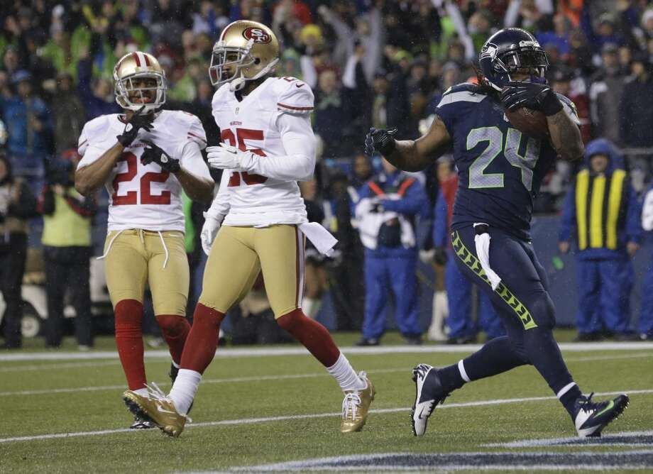 Seattle Seahawks' Marshawn Lynch (24) scores a touchdown as San Francisco 49ers' Carlos Rogers, left, and Tarell Brown, center, look on in the first half of an NFL football game, Sunday, Dec. 23, 2012, in Seattle. (Elaine Thompson / Associated Press)