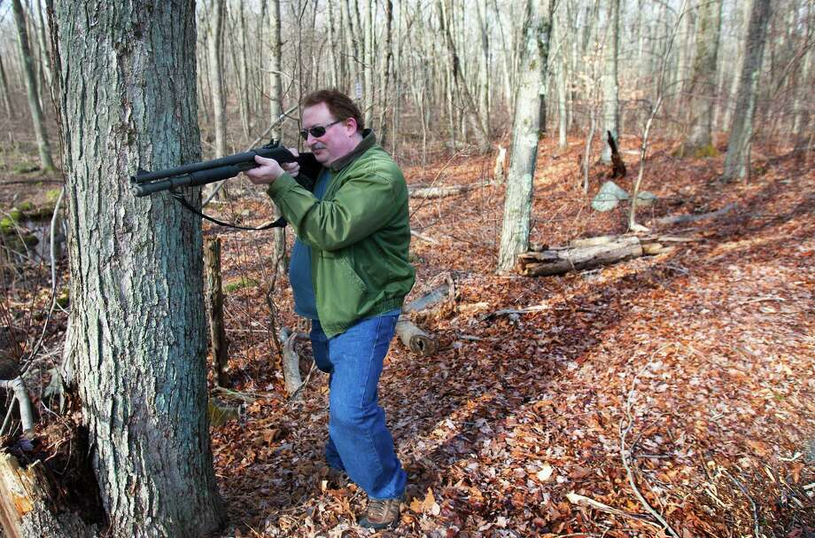 "Adam Palmer holds up a shotgun in the woods Sunday, Dec. 23, 2012, in Ansonia. Palmer believes in being prepared with the right tools in case events take place such as natural disasters. ""Every gun is a tool,"" Palmer said. ""Like a shovel, every tool has its purpose."" ( Cody Duty / Hearst Newspapers ) Photo: Cody Duty, Cody Duty/Hearst Newspapers / The News-Times"
