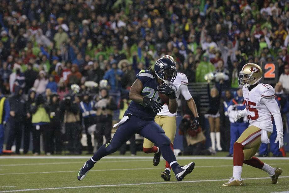 Seattle Seahawks' Marshawn Lynch scores his second touchdown of the game against the San Francisco 49ers in the first half of an NFL football game as San Francisco 49ers' Tarell Brown looks on at right, Sunday, Dec. 23, 2012, in Seattle.  (Elaine Thompson / Associated Press)