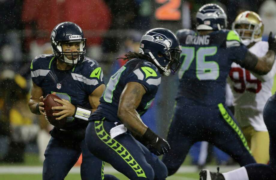 Seattle Seahawks quarterback Russell Wilson, left, looks to pass as Seahawks' Marshawn Lynch, second from left, moves past him in the first half of an NFL football game against the San Francisco 49ers, Sunday, Dec. 23, 2012, in Seattle. Photo: AP
