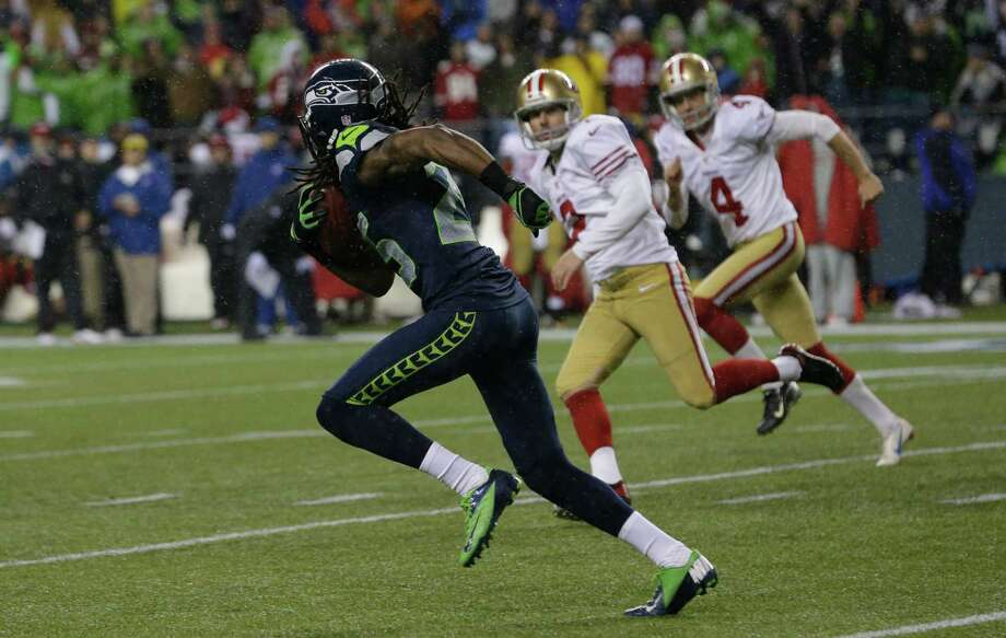Seattle Seahawks' Richard Sherman, left, runs for a touchdown after he scooped up a blocked field goal attempt  as San Francisco 49ers kicker David Akers (2) and holder Andy Lee (4) looks on in the first half of an NFL football game, Sunday, Dec. 23, 2012, in Seattle. Photo: AP
