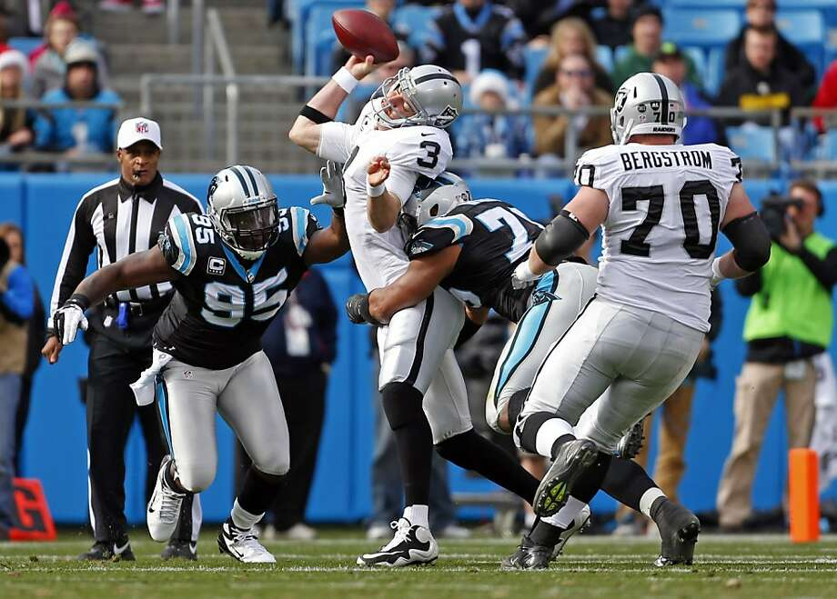 Oakland Raiders' Carson Palmer (3) is hit by Carolina Panthers' Greg Hardy (76) and Charles Johnson (95) while throwing a pass during the first half of an NFL football game in Charlotte, N.C., Sunday, Dec. 23, 2012. Palmer was taken off the field after the play and Hardy was penalized for a personal foul. (AP Photo/Bob Leverone) Photo: Bob Leverone, Associated Press