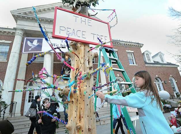 Courtney Coffey, 11, of Lake Katrine, N.Y., places a colored-paper branch into the peace tree in front of Newtown's Edmond Town Hall in memory of the victims of the Sandy Hook Elementary School shooting, in Newtown, Conn., Saturday, Dec. 22, 2012. Photo: Bob Luckey