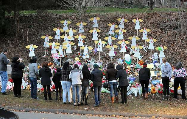 A crowd gathers in front of a memorial with 26 cardboard angels to the victims of the Sandy Hook Elementary School massacre on Church Hill Road, Newtown, Conn., Saturday, Dec. 22, 2012. Photo: Bob Luckey