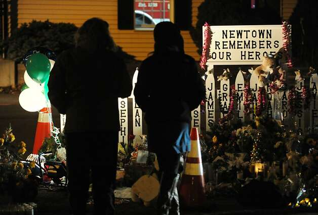 Two people stand near a memorial to the victims of the Sandy Hook Elementary School massacre on Dickinson Drive in Newtown, Conn., Saturday night, Dec. 22, 2012. Photo: Bob Luckey