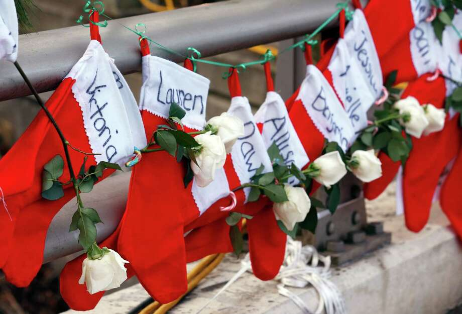 Stockings with victims' names hang from a railing in a makeshift memorial near the town Christmas tree in the Sandy Hook village of Newtown, Conn., as the community tries to find meaning in this year's holiday. Photo: Julio Cortez, STF / AP