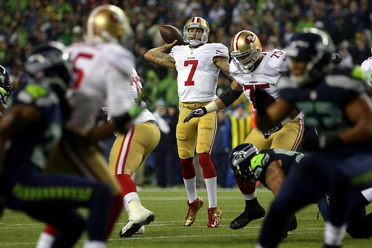 Colin Kaepernick, center, quarterback of the San Francisco 49ers, looks for a teammate to pass to during the first half of the Seahawks and 49ers game Sunday, Dec. 23, 2012, at CenturyLink Field in Seattle, WA.