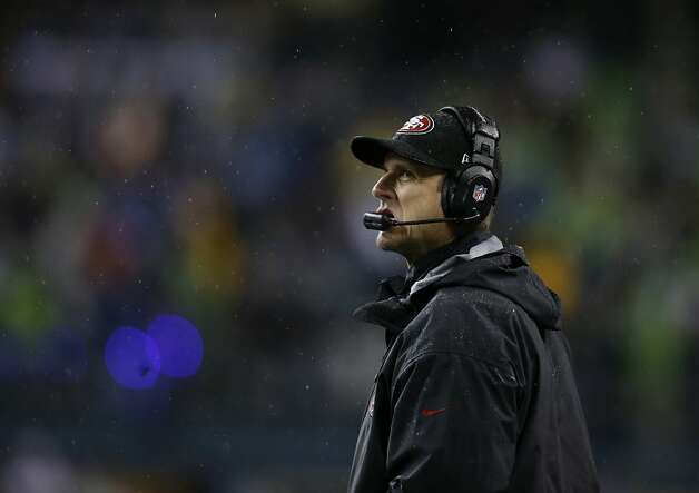 Jim Harbaugh glances at the scoreboard, where the news got progressively worse. Photo: John Froschauer, Associated Press