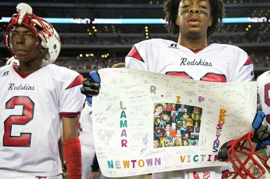Lamar defensive back Lee Duncan (36) holds a poster showing support of the victims of the Newtown school shooting before the Class 5A Division I state championship football game against Allen. Photo: Smiley N. Pool, Houston Chronicle / © 2012  Houston Chronicle