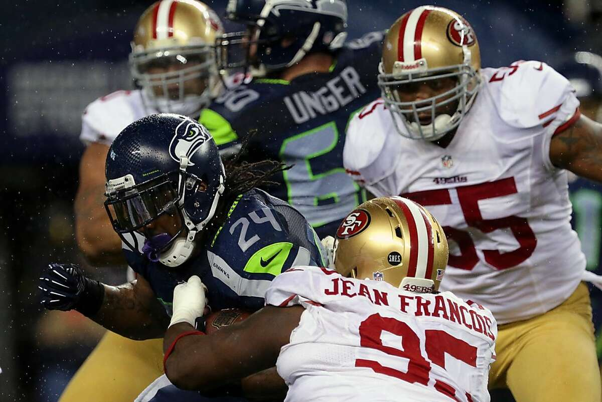 Marshawn Lynch, left, of the Seattle Seahawks, pushes through 49er defense during the first half of a game Sunday, Dec. 23, 2012, at CenturyLink Field in Seattle, WA.