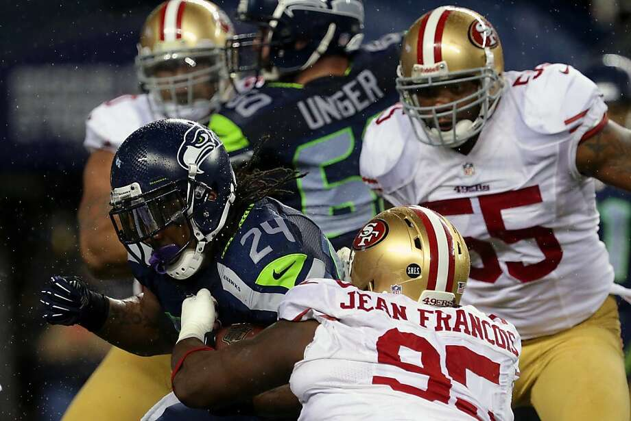 Marshawn Lynch, left, of the Seattle Seahawks, pushes through 49er defense during the first half of a game Sunday, Dec. 23, 2012, at CenturyLink Field in Seattle, WA. Photo: Jordan Stead, Special To The Chronicle