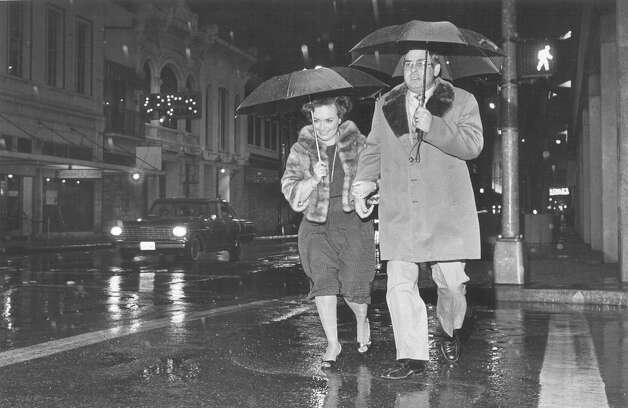 Roger and Esther DeHaven walk through the rain in the 200 block of E. Commerce Street on Friday night, Jan. 11, 1985. Photo: San Antonio Express-News File Photo