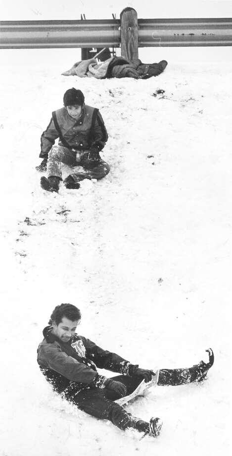 Joe Gomez (bottom) sleds down the Interstate 10 embankment at the Fresno overpass on Jan. 13, 1985. Photo: San Antonio Express-News File Photo