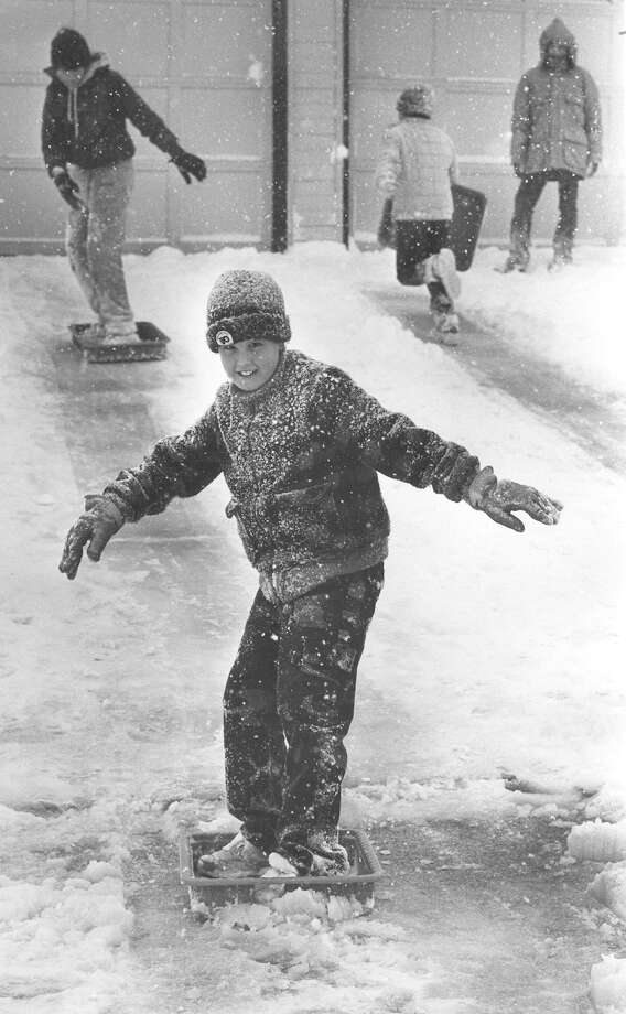 Scott Hegewald, 8, uses a pan to sled down a driveway in the 8700 block of Welles Edge in January 1985. Photo: San Antonio Express-News File Photo