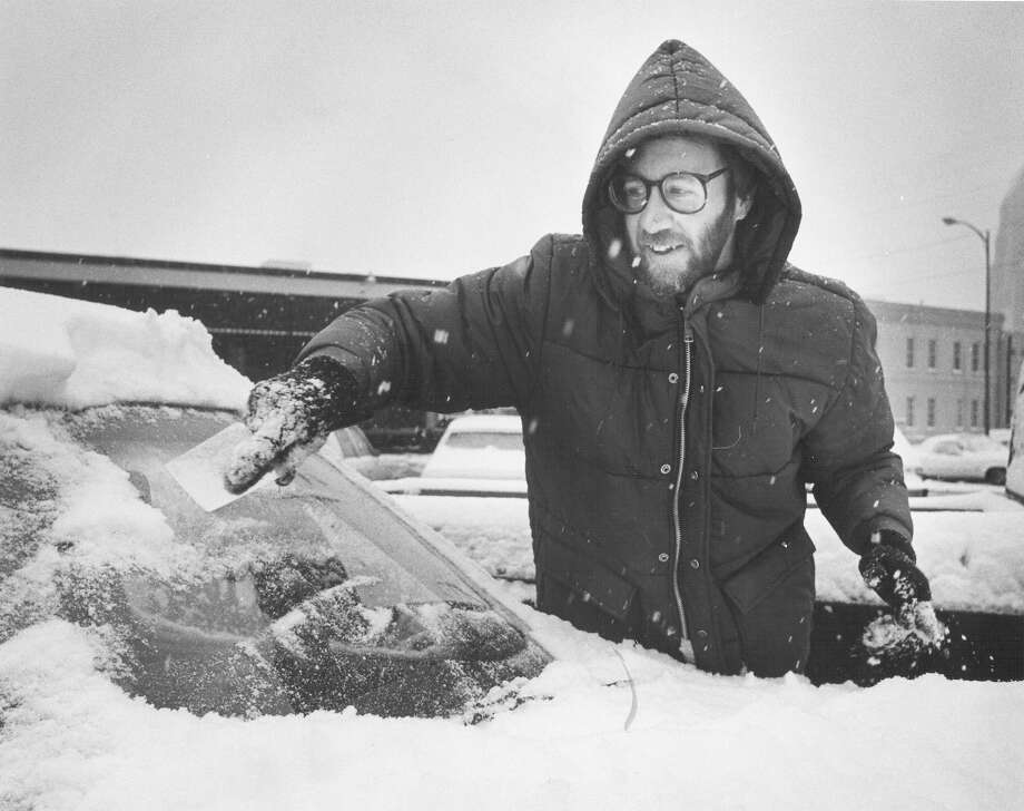 A man uses a piece of paper to clean snow from the windshield of his car on Jan. 12, 1985. Photo: San Antonio Express-News File Photo