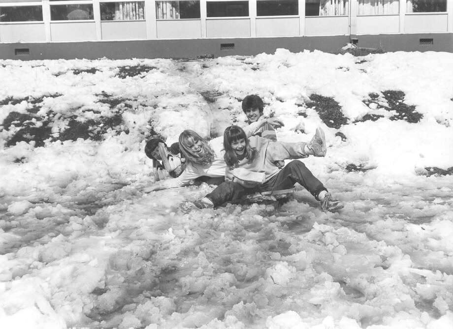 Children attempt to sled down a hill of melting snow on Jan. 15, 1985. Photo: San Antonio Express-News File Photo