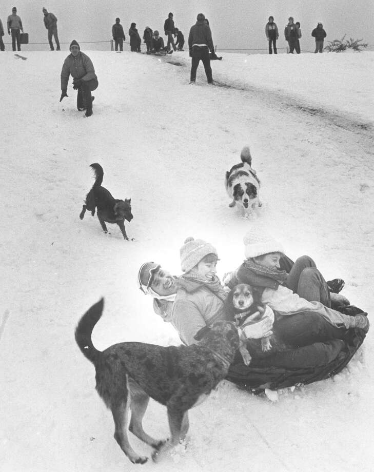 Brent Douglass, 29, wife Julie Douglass, 27, and Cindy Eggenberger, 27, sled down a hill on piece of plastic at Hildebrand and Devine, behind Trinity University on Jan. 13, 1985. Photo: San Antonio Express-News File Photo