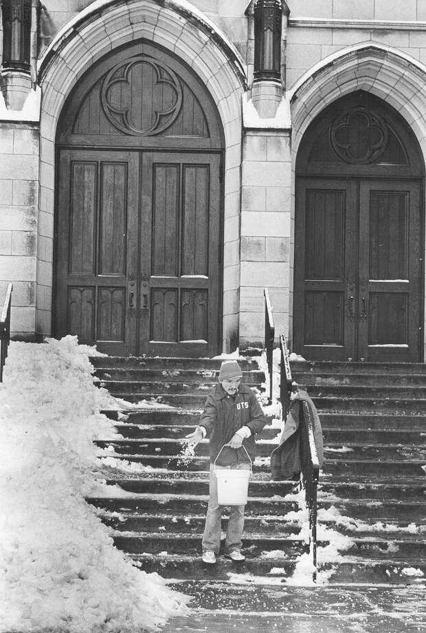 Groundskeeper Jeff Zoller salts the steps of the First Presbyterian Church on Jan. 13, 1985. Photo: San Antonio Express-News File Photo