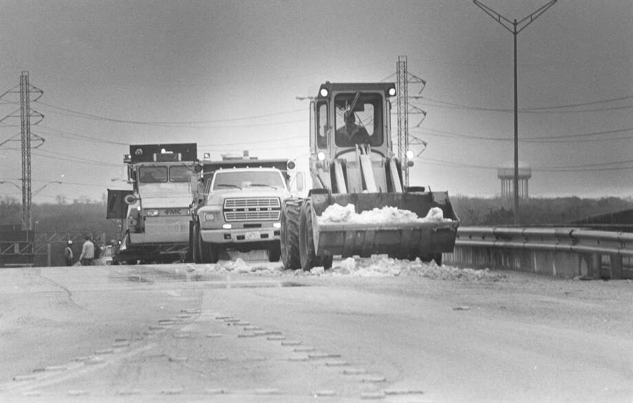 Plows and dump trucks work to clear the snow off Interstate 37 South on Jan. 16, 1985. Photo: San Antonio Express-News File Photo