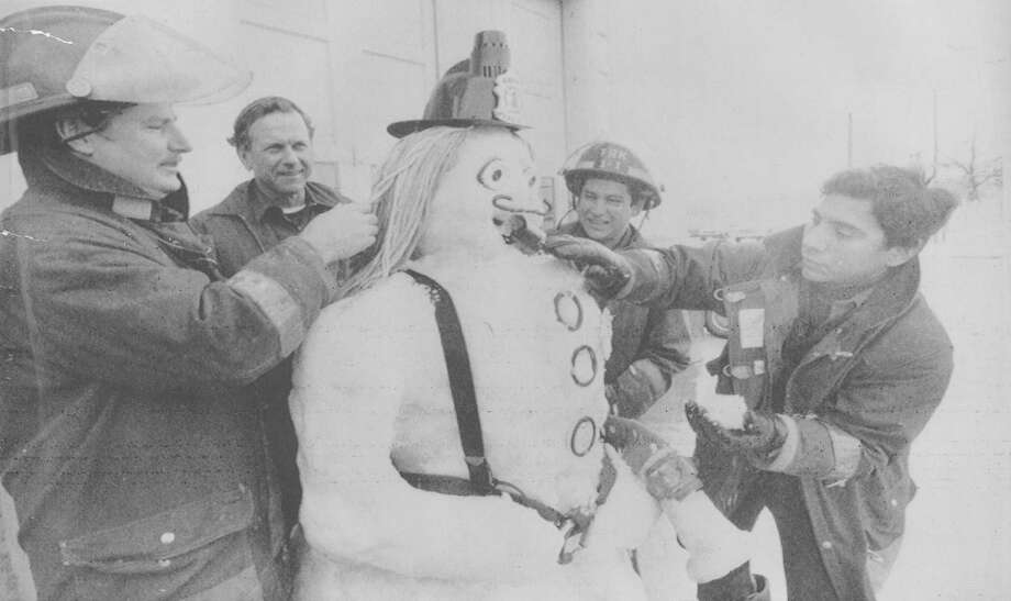 Members of the San Antonio Fire Department put the finishing touches on their snow person on Jan. 14, 1985. Sunny skies and warmer temperatures allowed many to enjoy the weekend's record snowfall. The firemen are Mike Miller (from left), Alex Bock, Roy Montejano and Carlos Quesada. They built their snow creation outside Fire Station No. 1. Photo: San Antonio Express-News File Photo