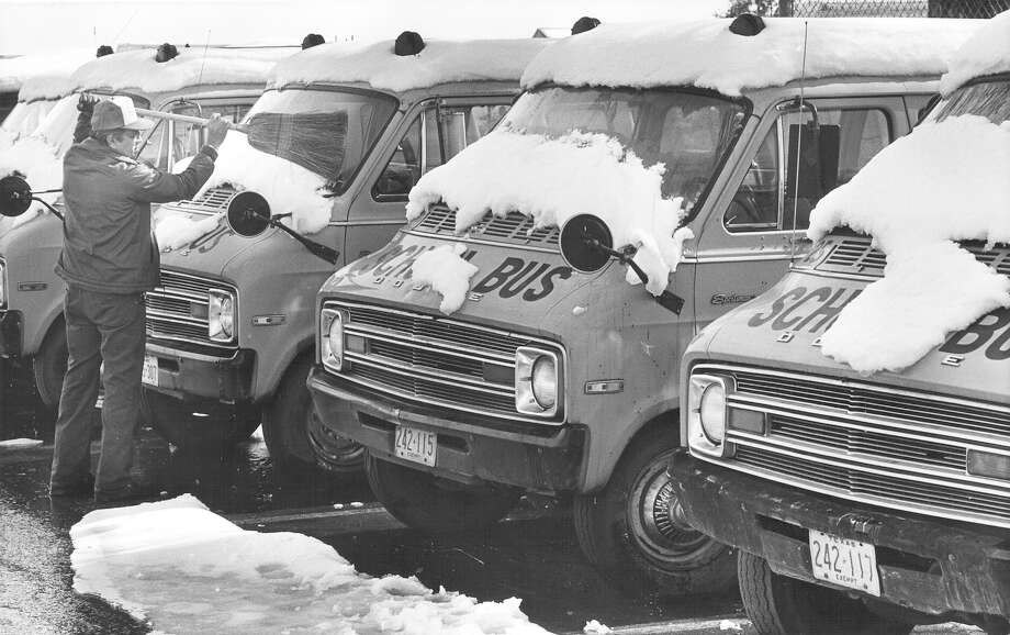 A man uses a broom to clean the snow off school buses in San Antonio in January 1985. Photo: San Antonio Express-News File Photo