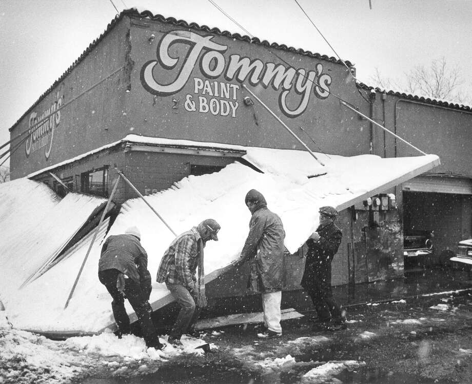 Tommy Calderon (from left), Rick Monster, Tomás Calderon and Harry Martinez lift the overhang of Tommy's Body Shop, 520 N. Zarzamora, after it collapsed under the weight of the falling snow on Jan. 12, 1985. Photo: San Antonio Express-News File Photo