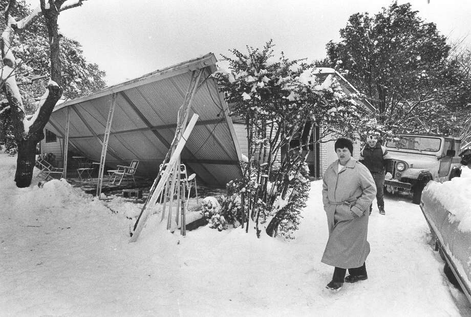 Ellen Blackmer walks by a home with a collapsed roof in the 200 block of Donnella Drive on Jan. 13, 1985. Photo: San Antonio Express-News File Photo