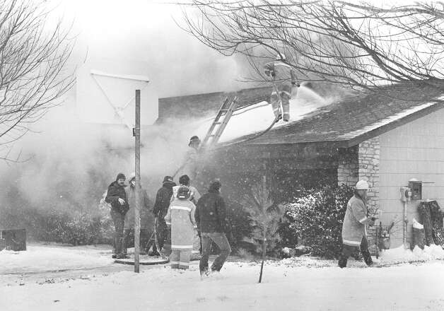 San Antonio firefighters put out a fire on New World Drive as snow falls in January 1985. Photo: San Antonio Express-News File Photo