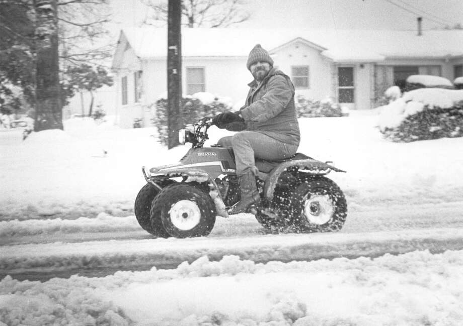 A man rides his 4-wheeler down a snowy Babcock Road on Jan. 13, 1985. Photo: San Antonio Express-News File Photo