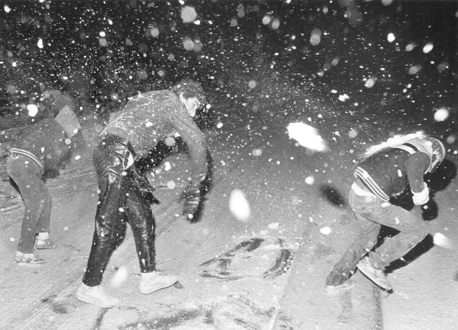 Kids have a snowball fight as snow started accumulating on the Guadalupe Street bridge in January 1985. Police had just closed the bridge. Photo: San Antonio Express-News File Photo