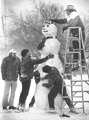 "Men work on an 8-foot-5-inch snowman at the corner of St. Cloud and Babcock Road on Jan. 12, 1985. ""We were a city of a million people and 500,000 snowmen,"" wrote the Light's Managing Editor Ed Raedemakers at the time. Photo: San Antonio Express-News File Photo"