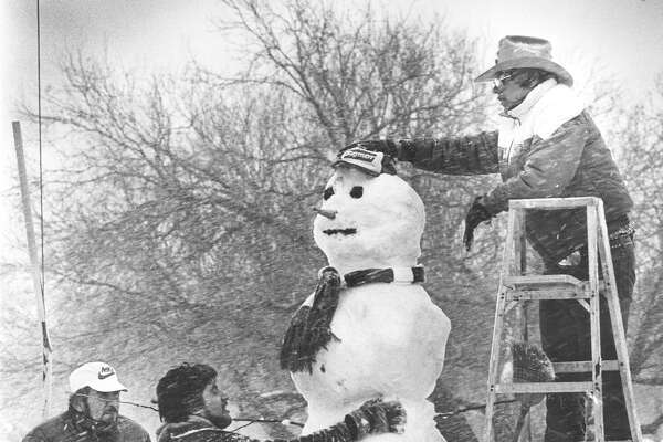 "Men work on an 8-foot-5-inch snowman at the corner of St. Cloud and Babcock Road on Jan. 12, 1985. ""We were a city of a million people and 500,000 snowmen,"" wrote the Light's Managing Editor Ed Raedemakers at the time."