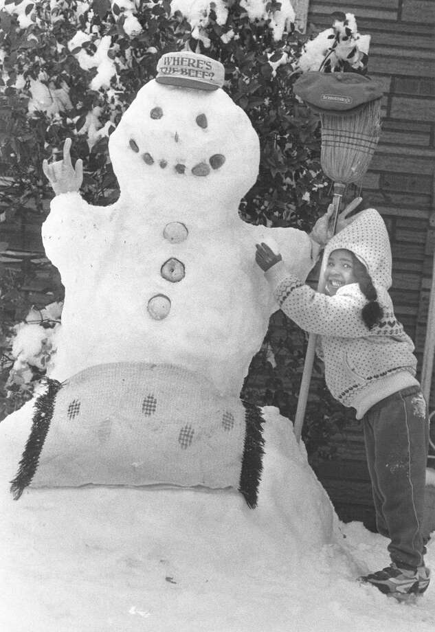 Latoya Simmons builds a snowman in front of her home in the 600 block of S. Polaris Street in January 1985. Photo: San Antonio Express-News File Photo