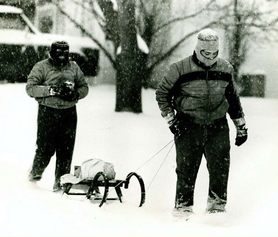 Rebecca and Bennie Lee take dinner supplies by sled from their grandparents to their home a few blocks away on Jan. 12, 1985. Photo: San Antonio Express-News File Photo