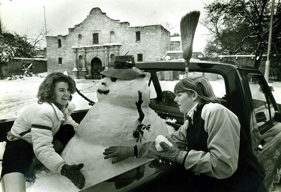 Two girls work on a snowman in the bed of a pickup in front of the Alamo on Jan. 12, 1985. Photo: San Antonio Express-News File Photo