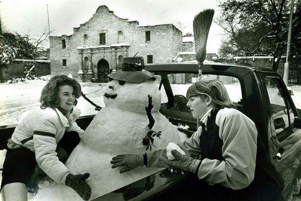 Two girls work on a snowman in the bed of a pickup in front of the Alamo on Jan. 12, 1985.
