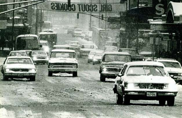 Drivers make their way down Houston Street while snow falls on San Antonio in January 1985. Photo: San Antonio Express-News File Photo